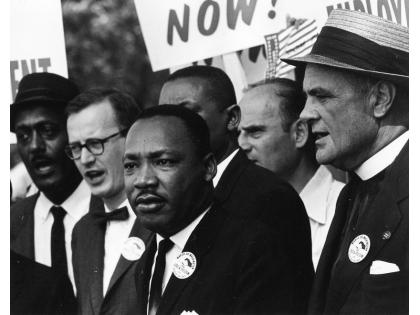 "[Rowland Scherman, Martin Luther King Jr. e Mathew Ahmann in mezzo alla folla durante la Marcia per i Diritti Civili (è in questa occasione che è stato pronunciato da Martin Luther King, davanti al Lincoln Memorial, il suo più famoso discorso dal titolo ""I have a dream""), 28 agosto 1963, Washington, D.C. (USA); courtesy: © U.S. Information Agency – Press and Publications Service / NARA – National Archives and Records Administration]"
